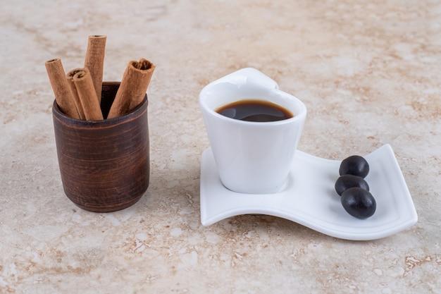 Gebundelde kaneelstokjes en een kopje koffie met snoepjes