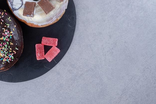 Gebundelde marmelades en twee donuts op een dienblad op marmeren oppervlak