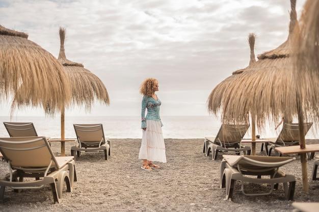Gecentreerde positie mooie blanke vrouw van middelbare leeftijd vrijheid in vrijetijdsbesteding buitenshuis op het strand met oceaan en wolken in de lucht stoelen en parasols plek en mode jurk mooi kort haar