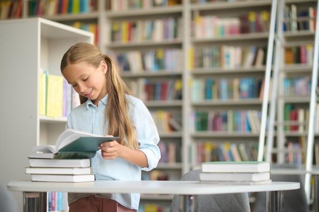 Geconcentreerd glimlachend blij schattig blond schoolkind dat voor een tafel staat met een stapel boeken