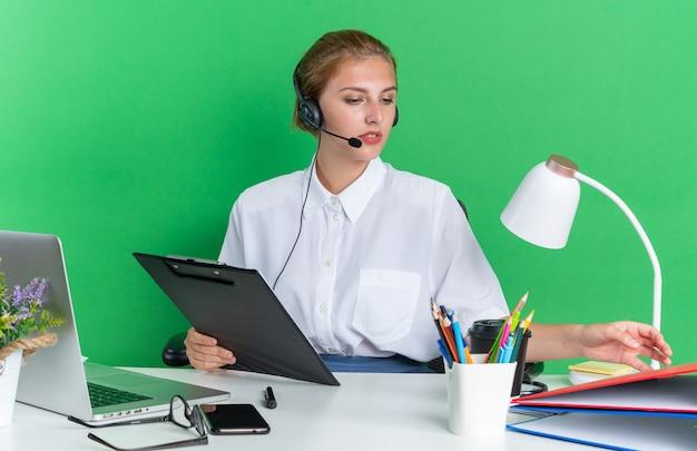 Geconcentreerd jong blond callcentermeisje met een hoofdtelefoon die aan een bureau zit met uitrustingsstukken die klembord vasthouden en naar de map kijken