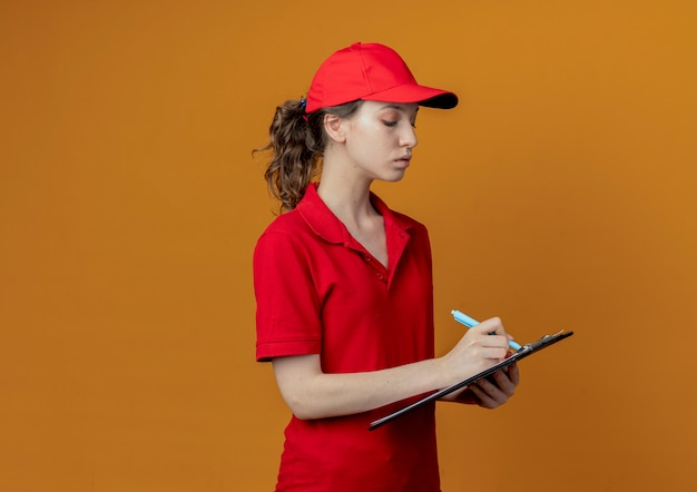 Geconcentreerd jong mooi leveringsmeisje in rood uniform en glb die op klembord met pen schrijven die op oranje achtergrond met exemplaarruimte wordt geïsoleerd