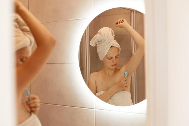 Geconcentreerd jong volwassen meisje dat oksel scheert in de badkamer, scheerapparaat in de hand houdt, naar haar lichaam kijkt, voorzichtig probeert te ontharen, gewikkeld in een witte handdoek.
