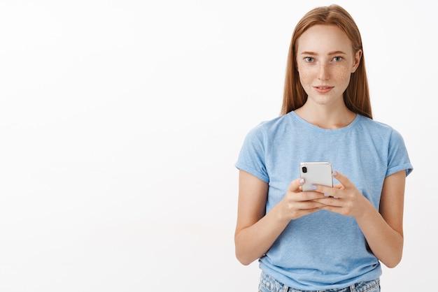Geconcentreerd kalm en ontspannen aangenaam aantrekkelijke roodharige vrouw met sproeten in blauw t-shirt met smartphone en staren geïnteresseerd aandacht trekken naar nieuwsgierig aanbod