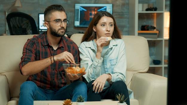 Geconcentreerd kaukasisch jong stel terwijl ze tv kijken en chips eten terwijl ze op de bank zitten.