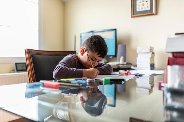 Geconcentreerd kind huiswerk in papa's kantoor
