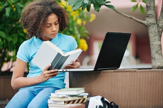 Geconcentreerd krullend gemengd ras schoolmeisje dat interessant boek leest op de campus