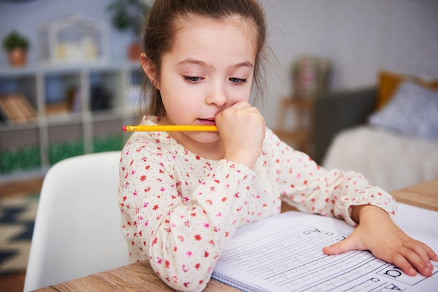 Geconcentreerd meisje dat haar huiswerk thuis doet