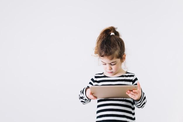 Geconcentreerd meisje die tablet gebruiken