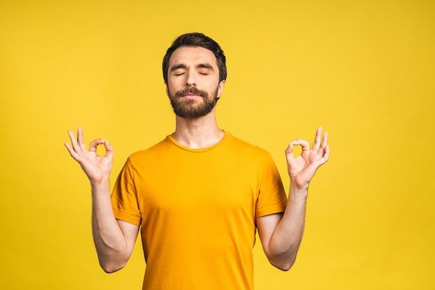 Geconcentreerd ontspannen persoon, staand met gesloten ogen, ontspannend tijdens het mediteren, proberen balans en harmonie te vinden. yoga en meditatie concept geïsoleerd op gele achtergrond.