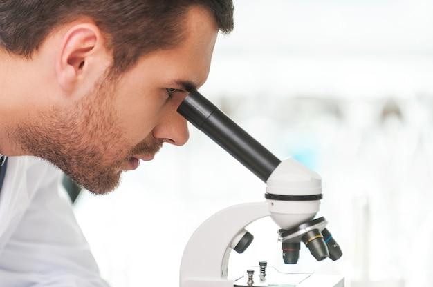 Geconcentreerd op genezing. zijaanzicht van jonge wetenschapper in wit uniform met behulp van microscoop terwijl hij op zijn werkplek zit
