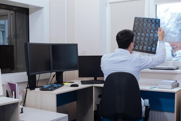 Geconcentreerd op het werk. ervaren knappe mannelijke radioloog zittend aan tafel en kijken naar de ct-scanfoto terwijl hij zich concentreerde op zijn taak