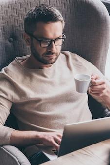 Geconcentreerd op het werk. knappe man die zijn laptop gebruikt en een koffiekopje vasthoudt terwijl hij in de stoel zit
