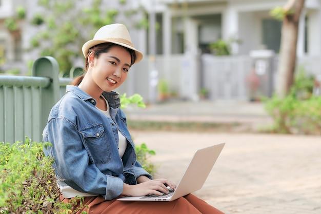 Geconcentreerd op het werk. zelfverzekerde jonge aziatische vrouw die casual draagt en op laptop werkt om overal op afstand te leren terwijl ze op de stad buiten zit.