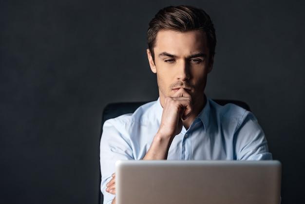 Geconcentreerd op het werk. zelfverzekerde knappe jongeman die naar zijn laptop kijkt
