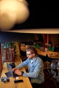 Geconcentreerd op werk kaukasische mannelijke ontwerper bezig met marketingproject in café, bekwame knappe fotograaf die ideeën opmerkt die geld verdienen bij het bewerken van afbeeldingen op laptop, in vrijetijdskleding