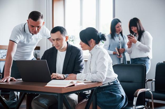 Geconcentreerd op werk. mensen uit het bedrijfsleven en manager werken aan hun nieuwe project in de klas