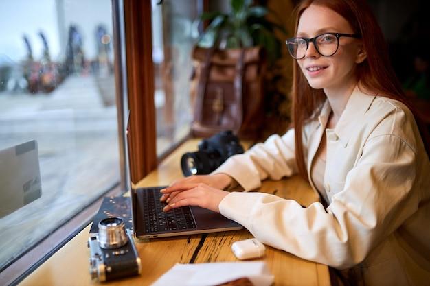 Geconcentreerd op werk roodharige vrouwelijke ontwerper in brillen bezig met marketingproject in café, bekwame vrouwelijke fotograaf die ideeën opmerkt die geld verdienen bij het bewerken van afbeeldingen op laptop, zijaanzichtportret