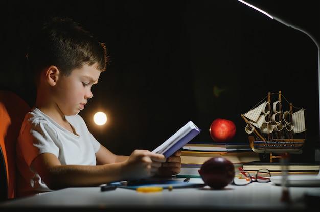 Geconcentreerd schooljongen leesboek aan tafel met boeken, plant, lamp, kleurpotloden, appel en leerboek