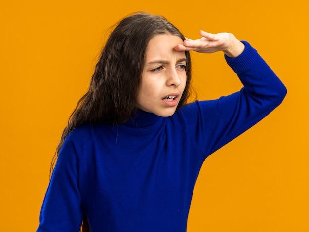 Geconcentreerd tienermeisje met loensende ogen die de hand op het voorhoofd houden en naar de zijkant kijken in de verte geïsoleerd op een oranje muur