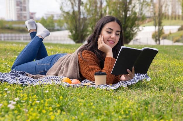 Geconcentreerd universiteitsmeisje dat voor test in openlucht bestudeert