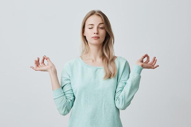 Geconcentreerde aantrekkelijke vrouw met lang geverfd haar gekleed in blauwe stands in lotus houding, mediteert en geniet van een rustige sfeer, sluit de ogen, probeert te ontspannen na een zware werkdag. mudra-gebaar