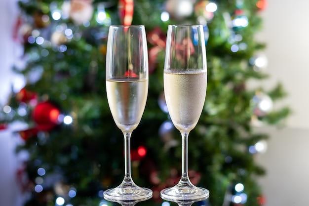 Geconcentreerde achtergrond met twee champagne-brillen op een donker glazen tafel voor een kerstboom