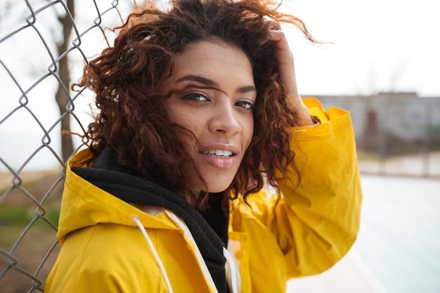 Geconcentreerde afrikaanse krullende jonge dame die gele jas draagt