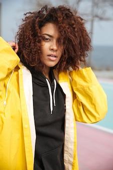 Geconcentreerde afrikaanse krullende jonge vrouw die gele laag draagt