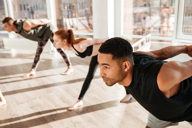 Geconcentreerde afrikaanse mens die yogaoefeningen in groep doen bij studio