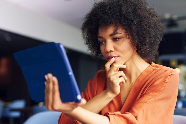 Geconcentreerde afrikaanse vrouw die met technologie werkt