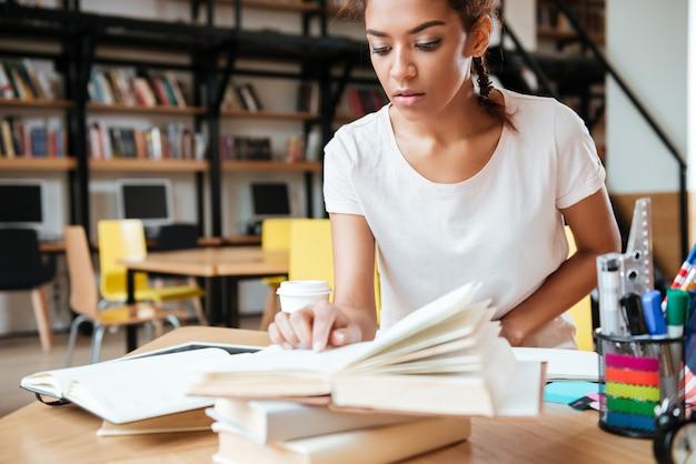 Geconcentreerde afrikaanse vrouw in bibliotheek