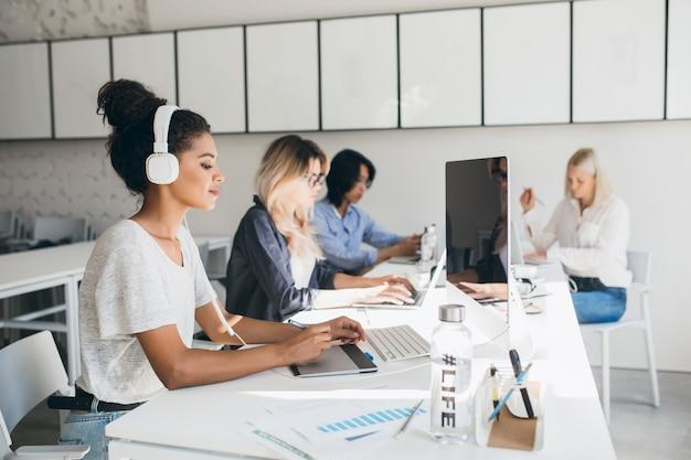 Geconcentreerde afrikaanse vrouwelijke webdesigner met grafisch tablet terwijl haar collega's rapporten schrijven. indoor portret van programmeurs van een internationaal bedrijf dat samen tijd doorbrengt op de werkplek.