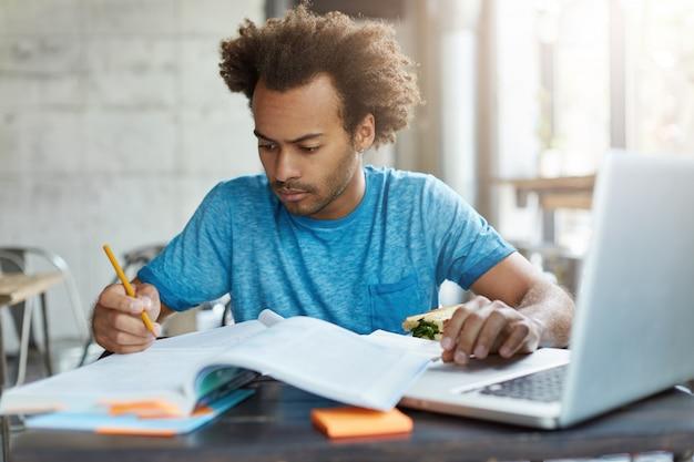 Geconcentreerde afro-amerikaanse hipster man in blauw t-shirt voorbereiding voor onderzoekstest schrijven van notities in zijn werkboek met laptopcomputer voor het zoeken van de nodige informatie