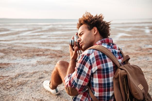 Geconcentreerde afro-amerikaanse jongeman met rugzak die buiten zit en foto's neemt