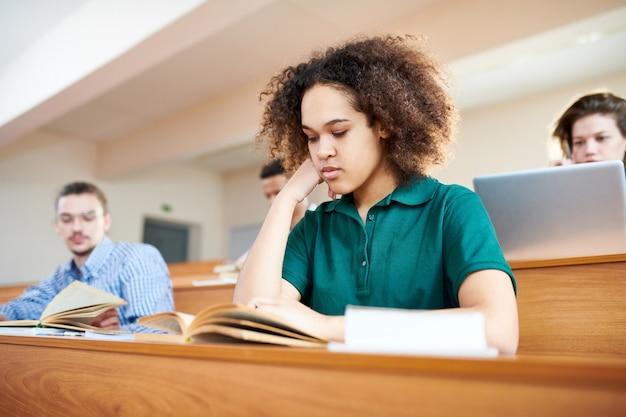 Geconcentreerde afro-amerikaanse student leerboek lezen