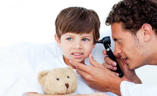 Geconcentreerde arts die de oren van de patiënt onderzoekt