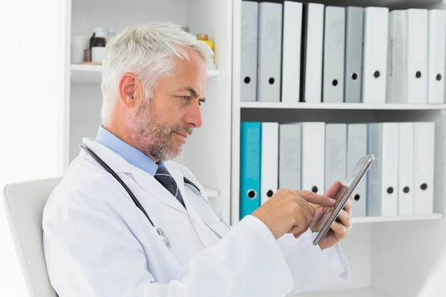 Geconcentreerde arts die digitale tablet op medisch kantoor gebruiken