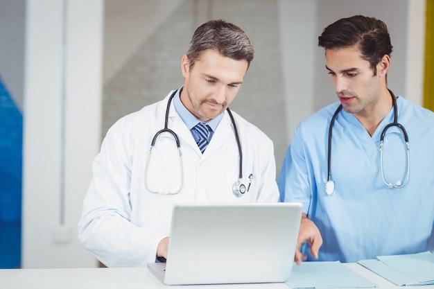 Geconcentreerde artsen die op laptop werken