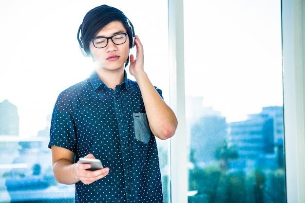 Geconcentreerde aziatische zakenman die aan muziek in bureau luistert
