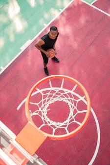 Geconcentreerde basketbalspeler die oefent voor basketbal en kijkt naar basketbalhoepel.