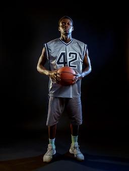 Geconcentreerde basketbalspeler houdt bal vast. professionele mannelijke baller in sportkleding die sportspel speelt, lange sportman