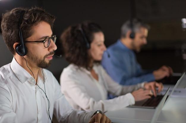 Geconcentreerde bebaarde call center operator werkt