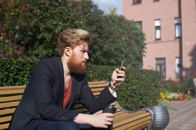 Geconcentreerde bebaarde hipster met smarphone terwijl hij op een bankje zit
