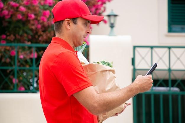 Geconcentreerde bezorger wandelen en lezen van adres op tablet. zijaanzicht van de koerier die bestelling in een papieren zak levert en een rood overhemd en een pet draagt. bezorgservice en online winkelconcept