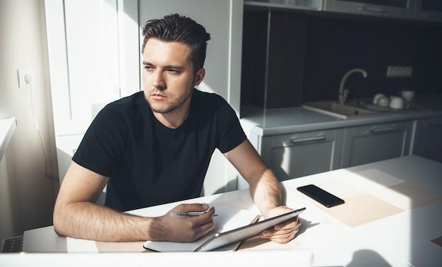 Geconcentreerde blanke man met modieus kapsel werkt op afstand vanuit huis en gebruikt tablet terwijl hij iets in de keuken schrijft