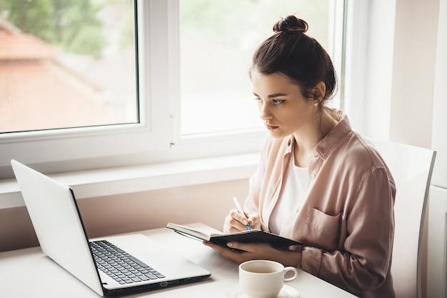 Geconcentreerde blanke vrouw in overhemd die een recept in het boek schrijft terwijl ze naar de laptop kijkt en een kopje thee drinkt bij het raam
