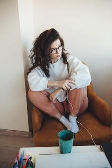 Geconcentreerde blanke vrouw met krullend haar en bril luisteren naar muziek zittend in een stoel en koffie drinken