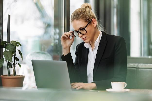 Geconcentreerde blonde bedrijfsvrouw die laptop computer met behulp van.