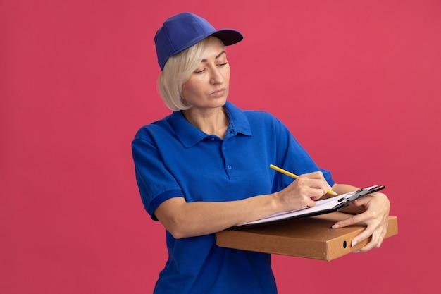 Geconcentreerde blonde bezorger van middelbare leeftijd in blauw uniform en pet schrijven met potlood op klembord met pizzapakket geïsoleerd op roze muur met kopieerruimte